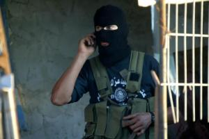 Palestinian terrorist talking on his sold-in-Israel cell phone.