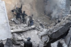 Syrian civilians attempt to put our a fire caused by a government airstrike on 27 February 2014 in the Aleppo neighbourhood of Kalase, Credit: EPA/ALI MUSTAFA