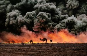 Struggling camels silhouetted against the oil-fire, Al-Ahmadi oil field, Kuwait in 1991. (Credit: Steve McCurry)