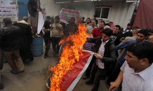 Palestinians burn Angola's flag in a protest amid reports that the country has banned Islam and destroyed mosques. (Credit: APA/Rex)