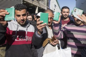 Former Palestinian employees of the Israeli SodaStream drinks firm show their identity cards before leaving the plant for the last time, victims of the failed BDS movement