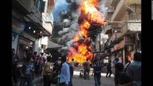 Residents run from a fire at a gasoline and oil shop in Aleppo. (Credit: CNN)